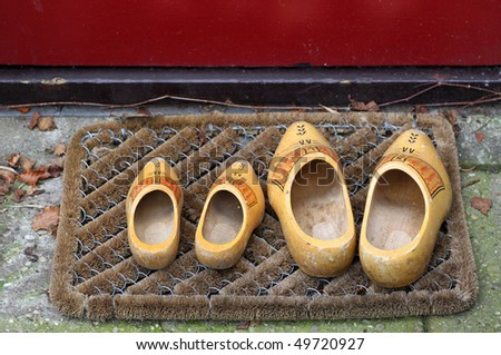 pair of traditional Dutch yellow wooden shoes outside a home on a door mat