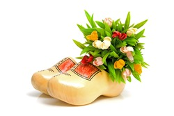 pair of traditional Dutch yellow wooden shoes with little tulips over white background