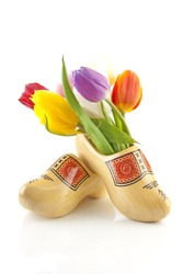 Pair of traditional yellow wooden shoes with colorful tulips isolated on white background