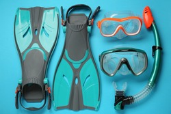 Pair of turquoise flippers and masks on light blue background, flat lay