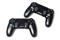Pair of two black video game controllers white background
