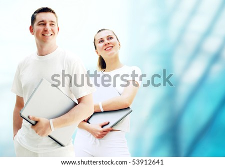 Pair of two happy young people or student with laptops on the business background