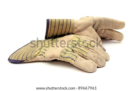 pair of used working gloves over white - stock photo