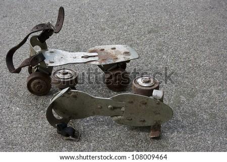 pair of vintage metal roller skates sitting on a cement sidewalk