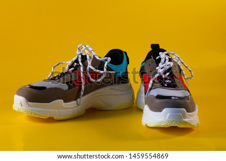 Pair of vintage sneakers / trainers on yellow background. Hipster footwear representing fashion for massive retro  shoes. Active lifestyle, fitness and sports concept.