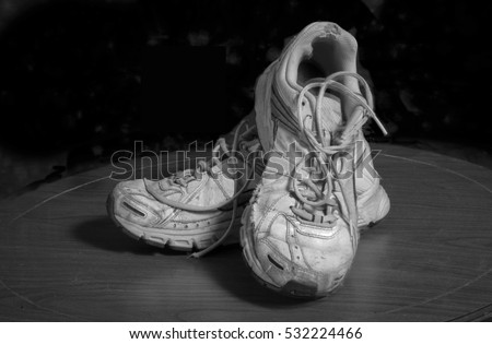 Pair of Well Worn Tennis Shoes Lit with Studio Lights. Black and White. Holes and Frays From Many Hours of Sports and Athletics.