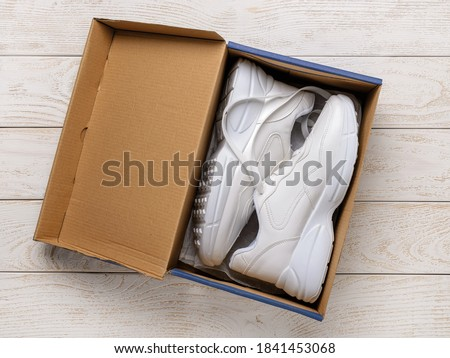 Pair of white chunky sole sneakers in a brown cardboard box on the white wood floor. Open box with new comfortable shoes for active lifestyle, fitness and sports. Top view. Сток-фото ©