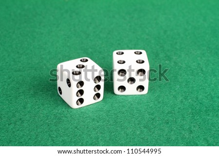 Pair of white dice on green felt with winning numbers seven and eleven showing in different combinations.