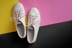 Pair of white gumshoes on colorful background.