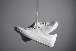 Pair of white gumshoes on grey background.