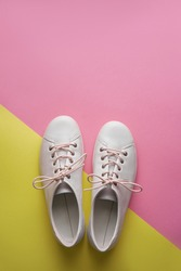 Pair of white gumshoes on pink-yellowl background.