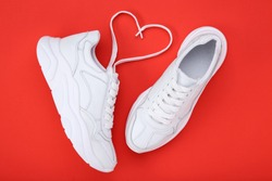 Pair of white shoes and shoelaces in shape of heart on red background