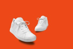 Pair of White sneaker isolated on orange background with clipping path