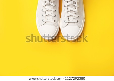 Pair of white sneakers on color background, top view