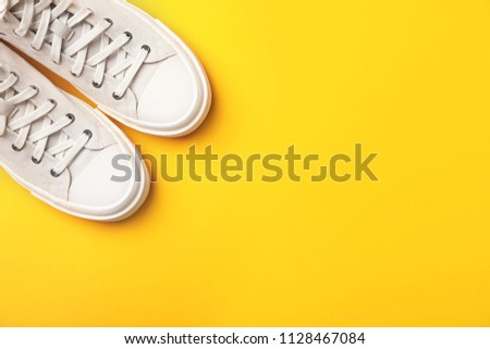 Pair of white sneakers on color background, top view #1128467084