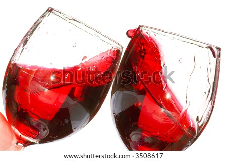 Pair of wine glasses making a toast with red wine