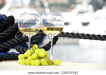 Pair of wineglasses and grapes against the yacht pier of La Spezia, Italy - stock photo