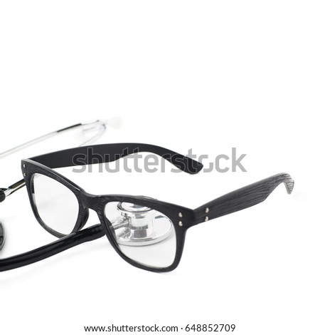 Pair of wooden textured optical reading glasses next to a medical stethoscope, composition isolated over the white background, close-up crop foreshortening #648852709