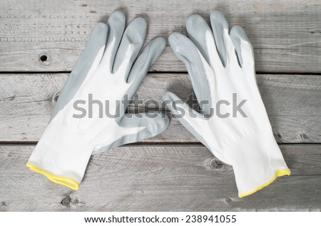 Pair of working gloves on vintage wooden table