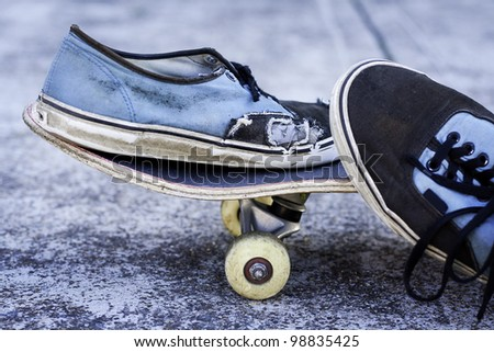 pair of worn out sneakers on a skateboard against concrete background