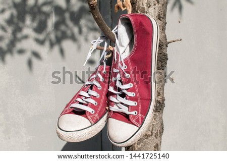 Pair of worn out vintage red old canvas sneakers hanging on their laced ties #1441725140