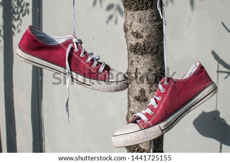 Pair of worn out vintage red old canvas sneakers hanging on their laced ties #1441725155