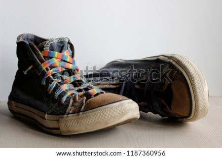 Pair of worn vintage blue sneakers with suede soles and rainbow laces. Hipster footwear for long road, travelling and hiking. Closeup photo of old boots representing retro grunge vibes.