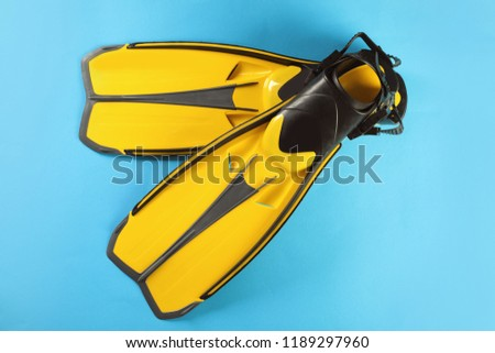 Pair of yellow flippers on color background, top view