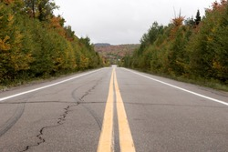 Pair of yellow lines on gray asphalt road. Canada