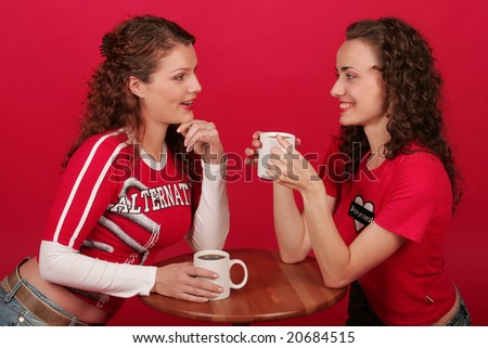 Pair of young beautiful women with cups of coffee in their hands