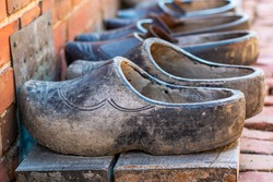 Pairs of old used dutch traditional wooden shoes or clogs in a row.