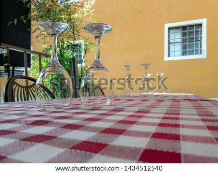 Pairs of the upturned empty wine glasses on the table covered by red and white checkered tablecloth in a street cafe.  Sets of the the transparent wine glasses. Selected focus with bokeh.