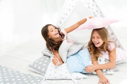 Pajamas party for kids. Girls having fun tipi house. Girlish leisure. Sisters share gossips having fun at home. Cozy place tipi house. Sisters or best friends spend time together lay in tipi house.
