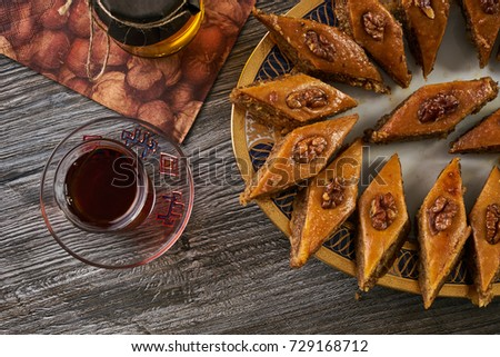 Pakhlava or baklava with nuts and honey. Novruz tray with Azerbaijan national pastry and drinking glass of black tea and honey jar on wooden table background, top view. Delicious dessert holiday food