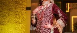 Pakistani Indian Desi bride showing her bridal dress on her wedding day