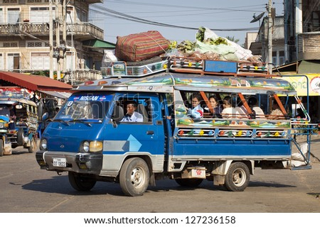 PAKSE, LAOS - JAN 13: A packed Songthaew taxi drives through the town of Pak Se in Laos on 13th January 2005. A Songthaew is a pick-up truck converted into a share taxi.