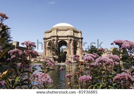 Palace of Fine Arts, San Francisco,California, looking across pond to dome pink flowers in foreground,blue sky in background.