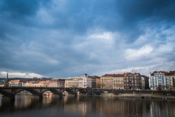 Palacky bridge over Vltava river in Prague, Czech Republic. Buildings and cloudy sky in the background. Space in the top side