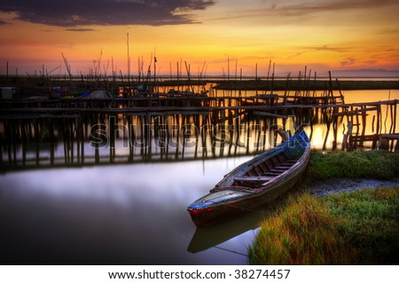 Palaffite port with row-boat in Carrasqueira, Portugal, at sunset