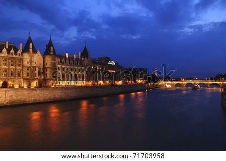 Palais de Justice standing on the banks of river Seine on the island Il de la Cite, Paris - France after the sunset