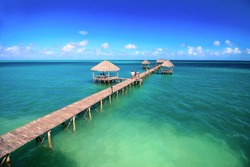 Palapas at the wooden peer on the tropical sea background, shallow focus