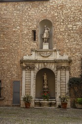 Palazzo Martinengo Cesaresco Novarino Palace. Courtyard with small fountain with beautiful statues and stone decor in shabby wall. Old sculpture with small fountain and plants and flowers in pots.