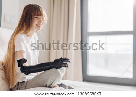 pale cheerful girl wearing a cyber hand sitting near the window in the clinic. copy space.innovation. the willingness to live