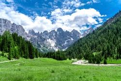 Pale di San Martino range panorama landscape during summer season. Passo Rolle summer landscape - Pale di San Martino range. Trentino Alto Adige. Mountain landscape in summer, Italian Dolomites.