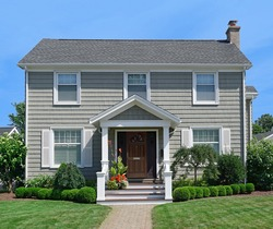 Pale green two story clapboard house with shrubbery and front lawn in summer