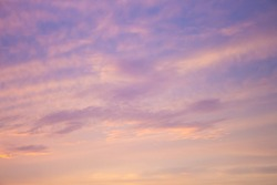 Pale lilac tinted clouds at sunset in tropical Broome, North Western Australia  are beautifully hued with soft pink and lavender tones as the hot sun sinks into the Indian Ocean in the summer Wet.