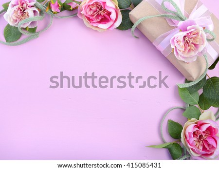 Pale pink feminine background with gift and silk roses on wood table with decorated borders, for Mothers Day, Valentine or feminine birthday or anniversary with copy space.