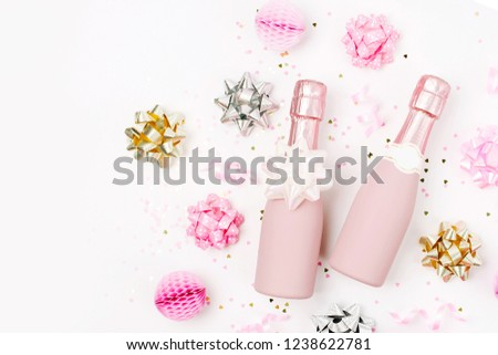 pale pink mini bottles of champagne with confetti and tinsel flat lay new year