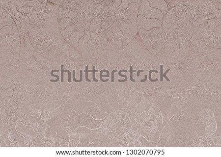 Pale pink nacreous color of abstract background of fossil Ammonites, Ammonoidea. Decorative pearl wallpaper of petrified shells. Print from textured spirals of seashells on light beige backdrop.