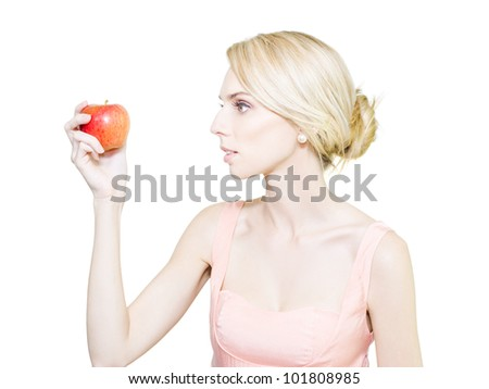 Pale thin undernourished woman who is fading away holding a tempting ripe red apple in her hand convinced that it will cause her to get fat
